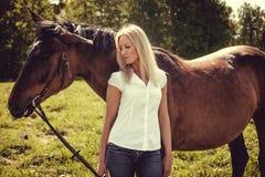 Blonde weibliche Aufstellung mit braunen Pferden auf einem Gebiet Stockfotos