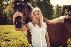 Blonde weibliche Aufstellung mit braunen Pferden auf einem Gebiet Lizenzfreie Stockfotografie