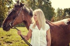Blonde weibliche Aufstellung mit braunen Pferden auf einem Gebiet Lizenzfreies Stockbild