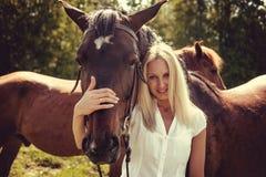 Blonde weibliche Aufstellung mit braunen Pferden auf einem Gebiet Stockbilder