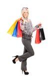 Blonde weibliche Aufstellung mit Einkaufenbeuteln Lizenzfreies Stockfoto