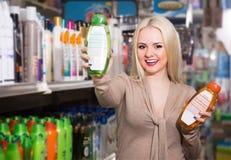 Blonde weibliche Aufstellung mit Flasche Shampoo Stockbild