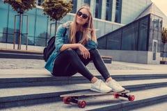Blonde weibliche Aufstellung mit longboard Lizenzfreies Stockfoto