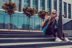 Blonde weibliche Aufstellung mit longboard Stockbilder