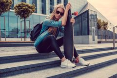 Blonde weibliche Aufstellung mit longboard Lizenzfreie Stockfotografie