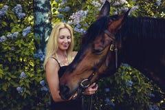 Blonde weibliche Aufstellung mit Pferd Lizenzfreie Stockfotos
