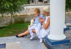 Blonde weibliche Entspannung mit ihrem Kind in einem Park Lizenzfreie Stockfotos