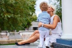 Blonde weibliche Entspannung mit ihrem Kind in einem Park Stockbilder