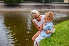 Blonde weibliche Entspannung mit ihrem Kind in einem Park Lizenzfreie Stockfotografie