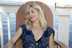 Blonde weibliche Entspannungstragende Badebekleidung am See Stockbild