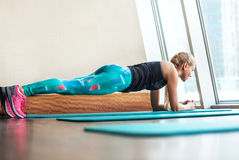Blonde weibliche Handelnstatische Übung der planke in der Turnhalle Stockfotografie