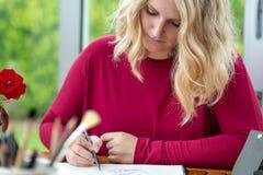 Blonde weibliche Künstlerzeichnung im Bleistift Stockfotos