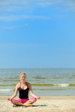 Blonde weibliche Meditation auf dem Strand Lizenzfreie Stockfotografie
