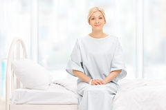 Blonde weibliche Patientenaufstellung gesetzt auf einem Krankenhausbett Lizenzfreies Stockbild