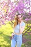 Blonde weibliche Person, die im Park mit Blütenhintergrund steht Stockfotos