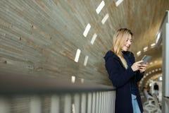 Blonde weibliche Person, die mit modernem Smartphone im monophonischen belichteten Hintergrund steht Stockbild