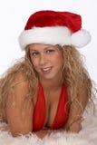 Blonde weibliche Sankt im roten Bikini, der auf Pelz-Wolldecke liegt Lizenzfreies Stockbild