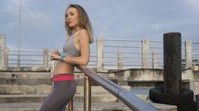 Blonde weibliche tragende Übungskleidung der Junge recht, die auf dem Pier nahe dem Meer steht und frühen Morgen genießt Lizenzfreie Stockbilder