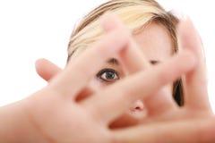 Blonde weibliche verstecken ihr Gesicht hinter ihrer Hand Lizenzfreies Stockbild