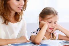 Blonde wenig Lesung zusammen mit Mutter Lizenzfreie Stockfotos