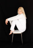 Blonde in white. Blond woman in white sitting on the chair stock images