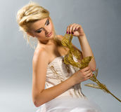 Blonde in white dress holding golden calla lilly Royalty Free Stock Images