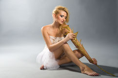 Blonde in white dress holding golden calla lilly Royalty Free Stock Image