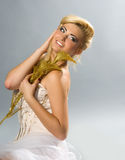 Blonde in white dress holding golden calla lilly Stock Photo