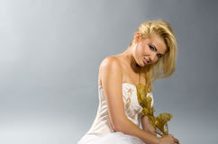 Blonde in white dress holding golden calla lilly Royalty Free Stock Photos