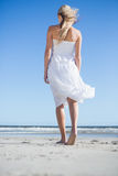 Blonde in white dress strolling on the beach Stock Image