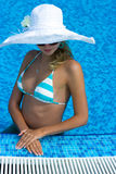 Blonde in white hat. Beautiful blonde girl in white hat sitting in the swimming pool Royalty Free Stock Image