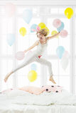 Blonde in a white pajamas jumping on the bed Royalty Free Stock Image