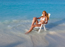 Blonde in white sexual bikini a beach chair at ocean in a sunny day Stock Image