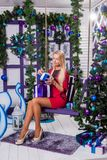 Blonde on a white terrace sitting on a swing in the New Year dec. Orations next to the Christmas tree decorated with Christmas balls and holding gifts Royalty Free Stock Images
