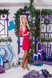Blonde on a white terrace sitting on a swing in the New Year dec. Orations next to the Christmas tree decorated with Christmas balls and holding gifts Stock Image
