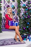 Blonde on a white terrace sitting on a swing in the New Year dec. Orations next to the Christmas tree decorated with Christmas balls and holding gifts Royalty Free Stock Image