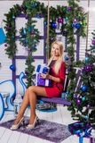 Blonde on a white terrace sitting on a swing in the New Year dec. Orations next to the Christmas tree decorated with Christmas balls and holding gifts Stock Images