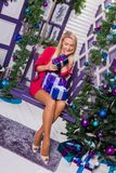 Blonde on a white terrace sitting on a swing in the New Year dec. Orations next to the Christmas tree decorated with Christmas balls and holding gifts Stock Photo