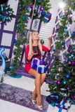 Blonde on a white terrace sitting on a swing in the New Year dec. Orations next to the Christmas tree decorated with Christmas balls and toss gifts to the top Stock Image