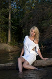 Sultry blonde woman sitting in river Stock Photography