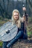 Blonde Wikinger-Kriegersfrau im Wald mit Schild und Klinge lizenzfreie stockbilder