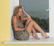 Blonde on the windowsill Stock Image