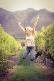 Blonde winegrower jumping in a vineyard Royalty Free Stock Photography