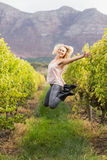 Blonde winegrower jumping in a vineyard Stock Photography