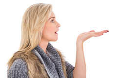 Blonde in winter clothes with hand out Royalty Free Stock Photos