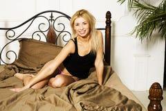 Blonde wirkliche Frau der Junge recht im Bett bedeckte Weißblätter smilin Lizenzfreie Stockfotos