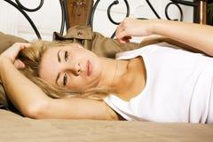 Blonde wirkliche Frau der Junge recht im Bett bedeckte Weißblätter smilin Lizenzfreie Stockfotografie
