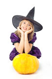 Blonde witch dreams on a pumpkin. Beautiful blonde witch sitting, dreams on a pumpkin Royalty Free Stock Image