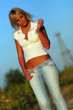 Blonde woman. Beautiful blonde woman on the country road with blue jeans and white shirt royalty free stock photos