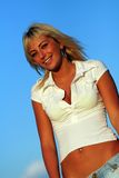 Blonde woman. Beautiful blonde woman with blue jeans and white shirt smiling, blue clear sky royalty free stock images